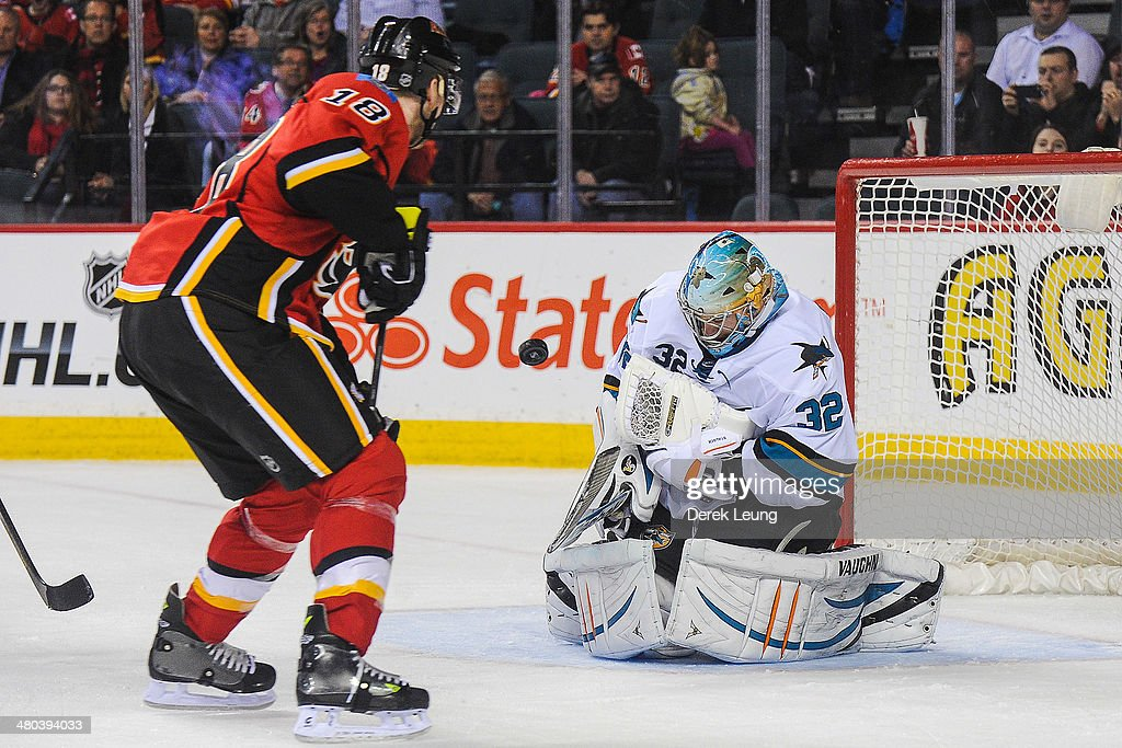 Matt Stajan #18 of the Calgary Flames takes a shot on <a gi-track='captionPersonalityLinkClicked' href=/galleries/search?phrase=Alex+Stalock&family=editorial&specificpeople=1966875 ng-click='$event.stopPropagation()'>Alex Stalock</a> #32 of the San Jose Sharks during an NHL game at Scotiabank Saddledome on March 24, 2014 in Calgary, Alberta, Canada. The Flames defeated the Sharks 2-1 in shootout.