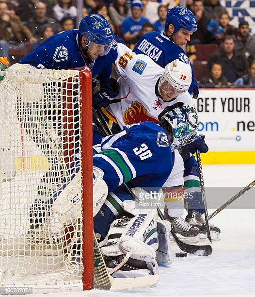 Matt Stajan of the Calgary Flames tries the jam the puck past goalie Ryan Miller of the Vancouver Canucks while Alexander Edler and Kevin Bieksa...
