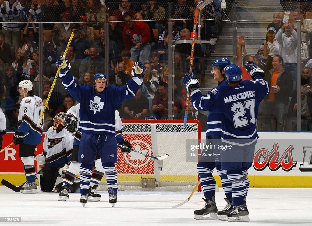 Matt Stajan #14 of the Toronto Maple Leafs celebrates with teammates Nik Antropov #80 and Bryan Marchment #27 after Antropov scored the opening goal of the game against the Washington Capitals at Air Canada Centre October 13, 2003 in Toronto, Ontario.