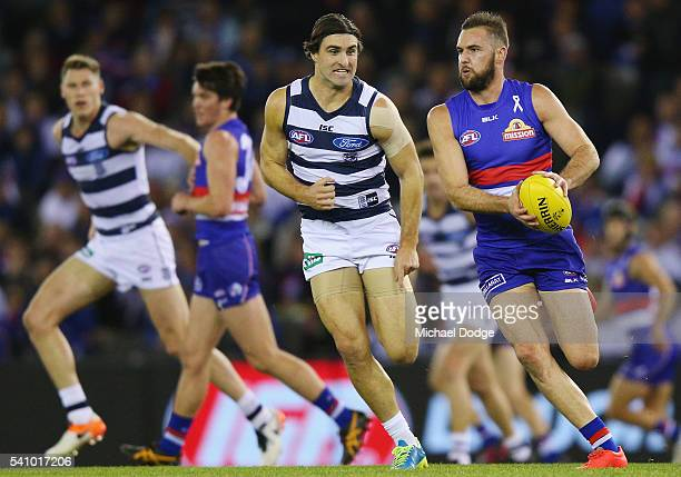 Matt Suckling of the Bulldogs runs with the ball away from Shane Kersten of the Cats during the round 13 AFL match between the Western Bulldogs and...