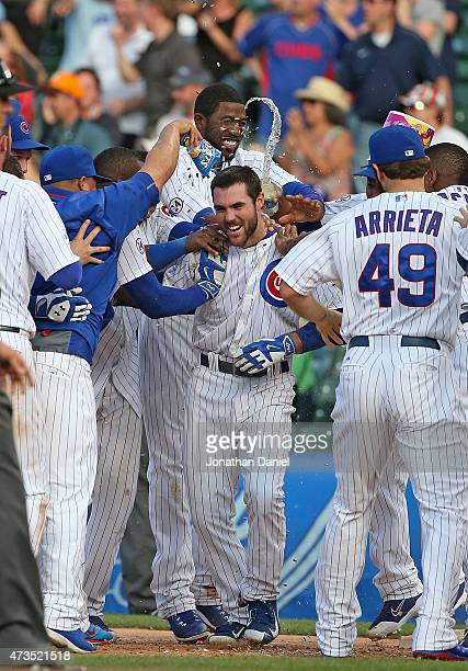 Matt Szczur of the Chicago Cubs is mobbed by teammates after getting the gamewinning hit in the 12th inning against the Pittsburgh Pirates at Wrigley...