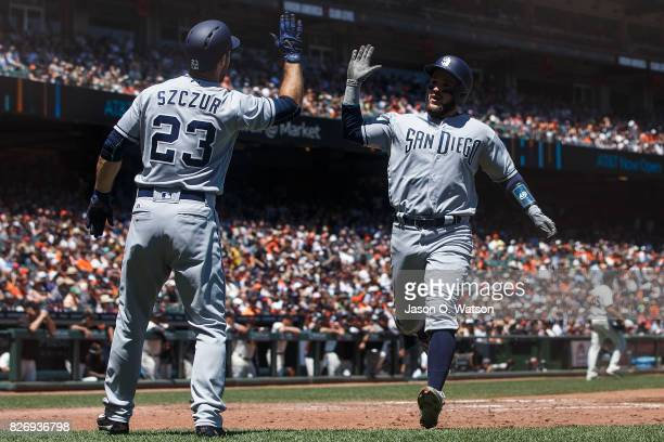 Matt Szczur of the San Diego Padres and Luis Torrens celebrate after both scored on a triple hit by Luis Perdomo during the fourth inning against the...