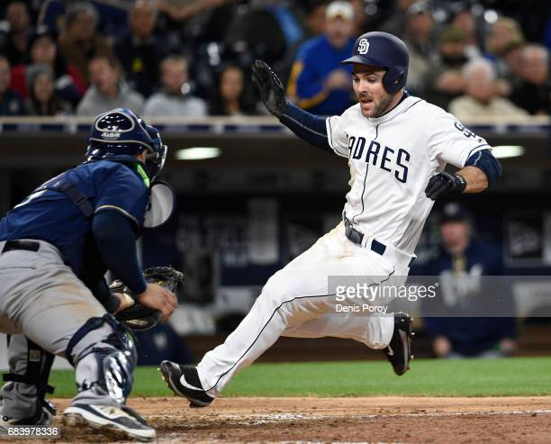 Matt Szczur of the San Diego Padres is tagged out at the plate by Manny Pina of the Milwaukee Brewers during the seventh inning of a baseball game at...