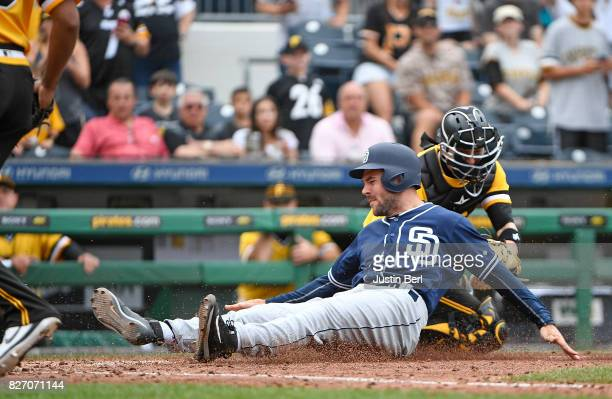 Matt Szczur of the San Diego Padres slides safely past Chris Stewart of the Pittsburgh Pirates to score on a two run single by Manuel Margot in the...