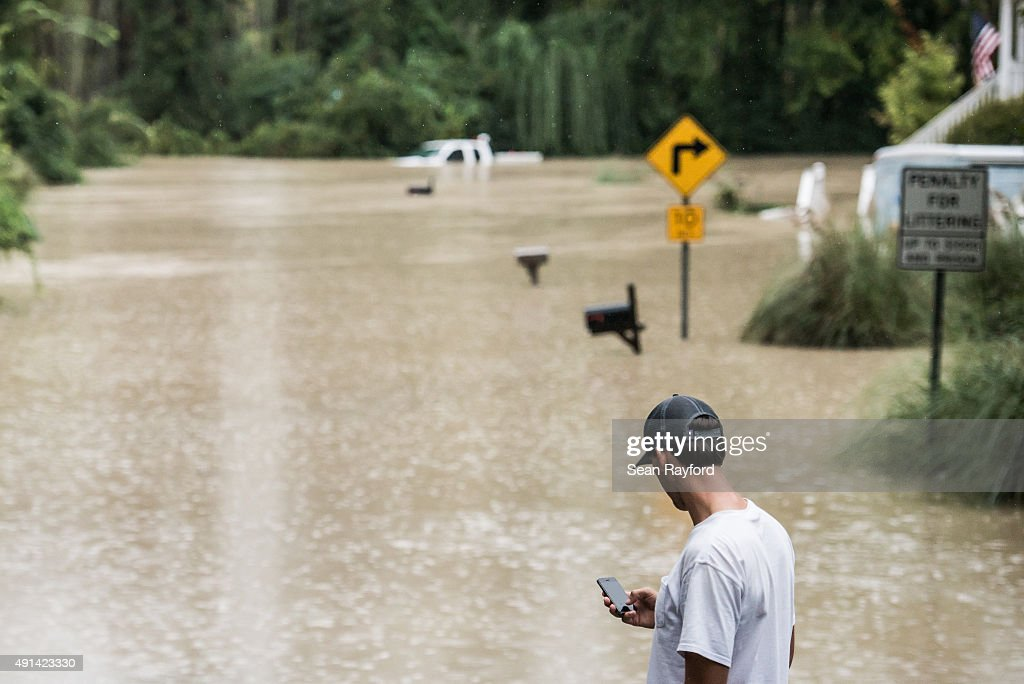 Matt Talley contacts a neighbor before taking a canoe to investigate his home following flooding in the area October 5 2015 in Columbia South...