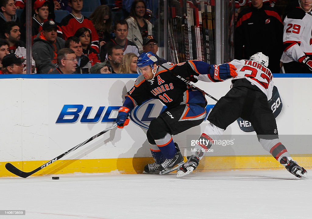 Matt Taormina #32 of the New Jersey Devils reaches out to slow down <a gi-track='captionPersonalityLinkClicked' href=/galleries/search?phrase=John+Tavares&family=editorial&specificpeople=601791 ng-click='$event.stopPropagation()'>John Tavares</a> #91 of the New York Islanders at Nassau Veterans Memorial Coliseum on March 4, 2012 in Uniondale, New York.