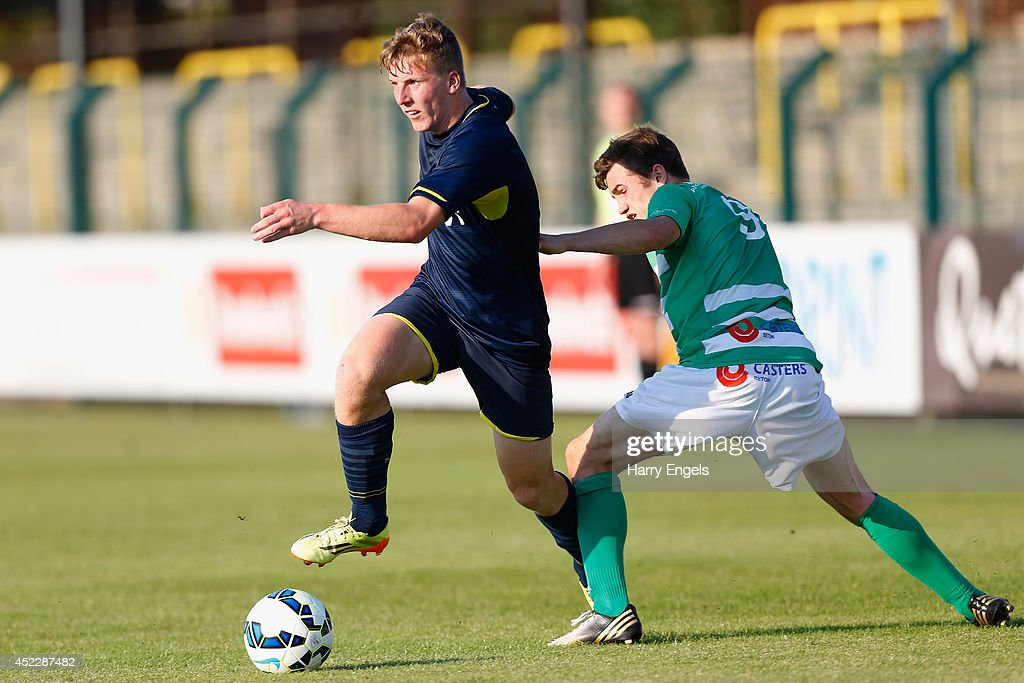 Matt Targett of Southampton avoids the tackle of Simen Demulder of KSK Hasselt during the pre-season friendly match between KSK Hasselt and Southampton at the Stedelijk Sportstadion on July 17, 2014 in Hasselt, Belgium.