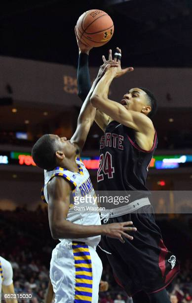 Matt Taylor of the New Mexico State Aggies is fouled by Dedrick Basile of the Cal State Bakersfield Roadrunners during the championship game of the...