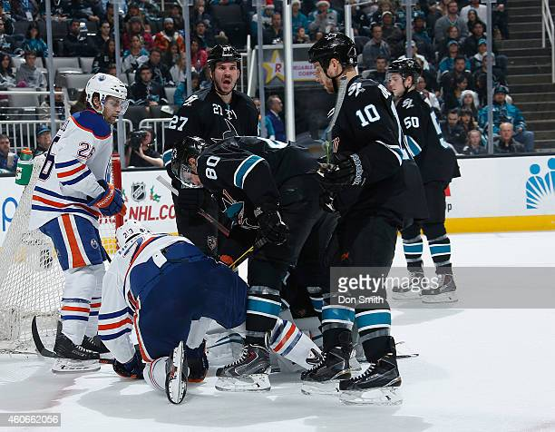 Matt Tennyson Andrew Desjardins and Scott Hannan of the San Jose Sharks look for a rebound against the Edmonton Oilers during an NHL game on December...