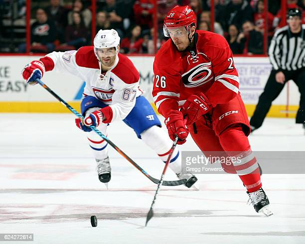Matt Tennyson of the Carolina Hurricanes is pursued by Max Pacioretty of the Montreal Canadiens during an NHL game on November 18 2016 at PNC Arena...