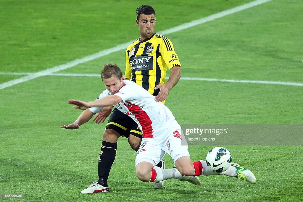 Matt Thompson of the Heart goes down in the tackle of Manny Muscat (R) of the Phoenix during the round 13 A-League match between the Wellington Phoenix and the Melbourne Heart at Westpac Stadium on December 27, 2012 in Wellington, New Zealand.