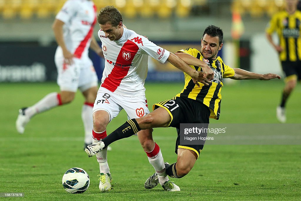 Matt Thompson of the Heart is tackled by Dani Sanchez of the Phoenix during the round 13 A-League match between the Wellington Phoenix and the Melbourne Heart at Westpac Stadium on December 27, 2012 in Wellington, New Zealand.