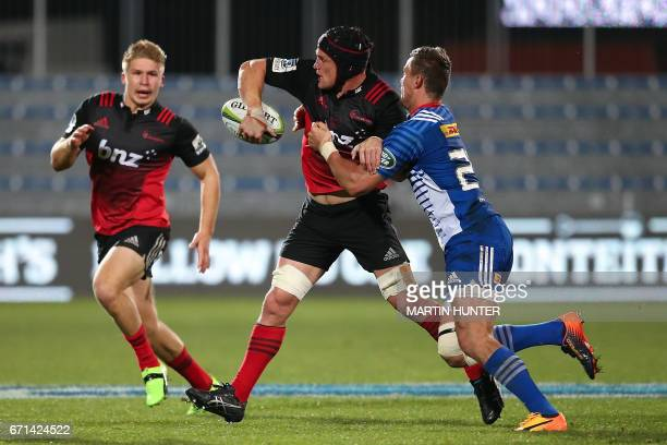 Matt Todd of the Canterbury Crusaders passes the ball in the tackle of Kurt Coleman of the Western Stormers during the Super Rugby match between New...