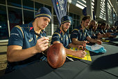 Matt Toomau of the Wallabies signs an old leather rugby ball during an Australian Wallabies fan day event at The Mondo on August 8 2014 in Penrith...
