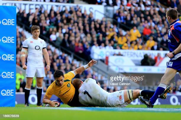 Matt Toomua of Australia scores the opening try despite the tackle from Chris Robshaw of England during the QBE International match between England...