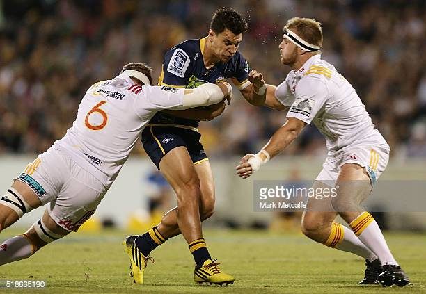 Matt Toomua of the Brumbies is tackled by Tom Sanders of the Chiefs and Sam Cane of the Chiefs during the round six Super Rugby match between the...