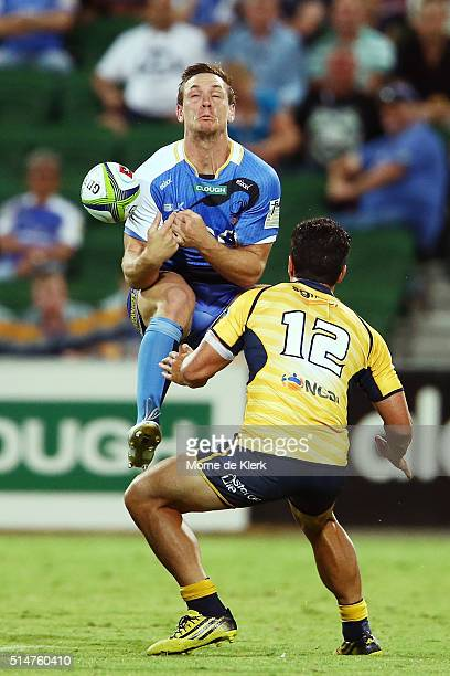 Matt Toomua of the Brumbies puts pressure on Dane HaylettPetty of the Western Force during the round three Super Rugby match between the Western...