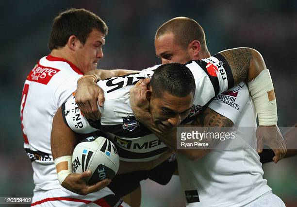 Matt Utai of the Tigers is tackled by Brett Morris and Matt Cooper of the Dragons during the round 22 NRL match between the Wests Tigers and the St...
