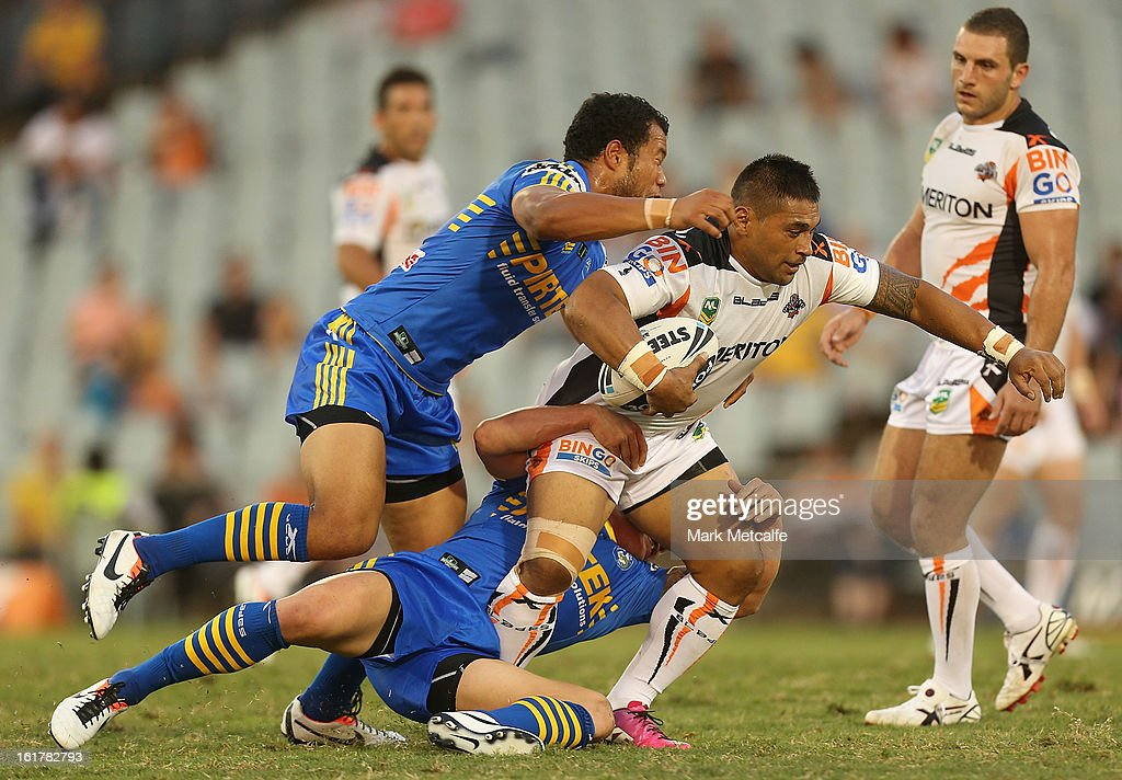<a gi-track='captionPersonalityLinkClicked' href=/galleries/search?phrase=Matt+Utai&family=editorial&specificpeople=214110 ng-click='$event.stopPropagation()'>Matt Utai</a> of the Tigers is tackled during the NRL trial match between the Wests Tigers and the Parramatta Eels at Campbelltown Sports Stadium on February 16, 2013 in Sydney, Australia.