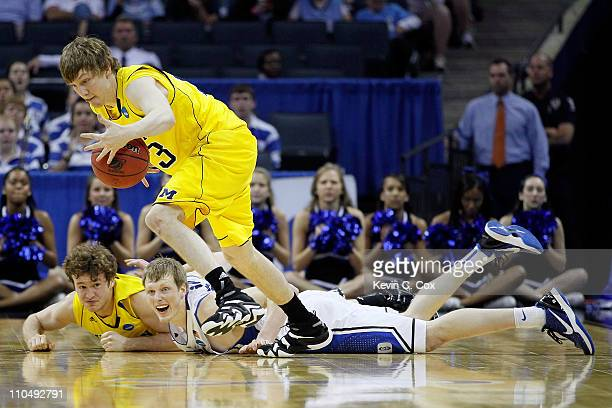 Matt Vogrich of the Michigan Wolverines picks up a loose ball in front of teammate Zack Novak and Kyle Singler of the Duke Blue Devils in the first...