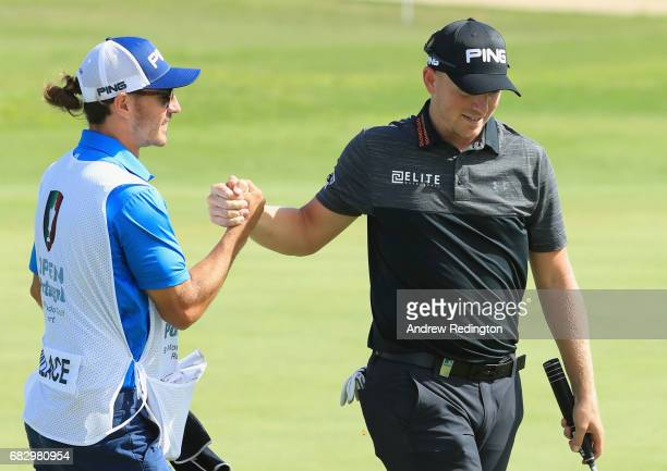 Matt Wallace of England celebrates victory on the 18th green with his caddie during the final round on day four of the Open de Portugal at Morgado...