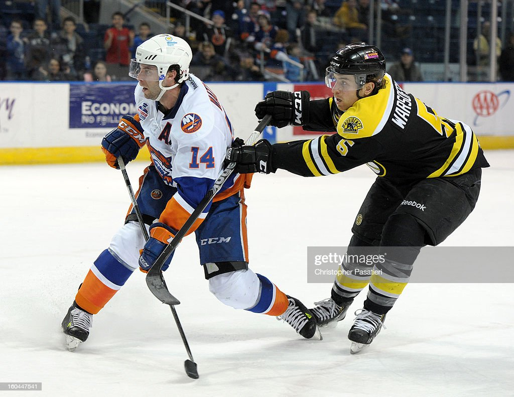 Matt Watkins #14 of the Bridgeport Sound Tigers is checked from behind by David Warsofsky #5 of the Providence Bruins after taking a shot on goal during overtime of an American Hockey League game on January 31, 2013 at the Webster Bank Arena at Harbor Yard in Bridgeport, Connecticut.