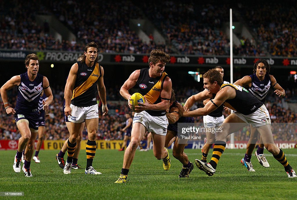 Matt White of the Tigers evades being tackled by Matt de Boer of the Dockers during the round five AFL match between the Fremantle Dockers and the Richmond Tigers at Patersons Stadium on April 26, 2013 in Perth, Australia.