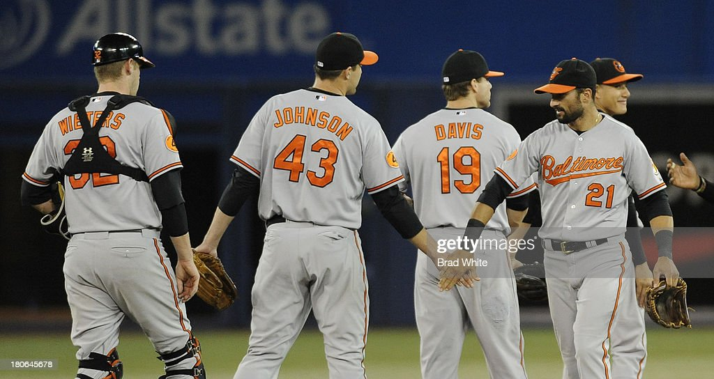 Matt Wieters #32, Jim Johnson #43, Chris Davis #19 and Nick Markakis #21 of the Baltimore Orioles celebrate the teams win over the Toronto Blue Jays during MLB game action September 15, 2013 at Rogers Centre in Toronto, Ontario, Canada.