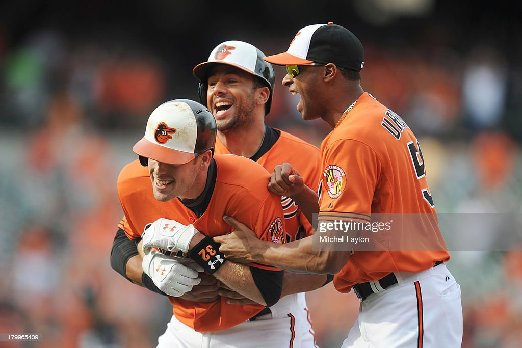 <a gi-track='captionPersonalityLinkClicked' href=/galleries/search?phrase=Matt+Wieters&family=editorial&specificpeople=4498276 ng-click='$event.stopPropagation()'>Matt Wieters</a> #32 of the Baltimore Orioles celebrates a walk off single with Chris Dickerson #36 and Henry Urrutia #51 in the tenth inning during a baseball game against the Chicago White Sox on September 7, 2013 at Oriole Park at Camden Yards in Baltimore, Maryland. The Orioles won 4-3 in the tenth inning.