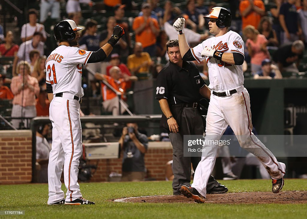 Matt Wieters of the Baltimore Orioles celebrates with teammate Nick Markakis after hitting a two RBI home run against the Tampa Bay Rays during the...