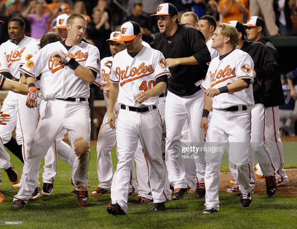Matt Wieters #32 of the Baltimore Orioles (L) is mobbed by teammates after hitting a walk off grand slam to give the Orioles a 10-6 win in ten innings at Oriole Park at Camden Yards on April 18, 2013 in Baltimore, Maryland.
