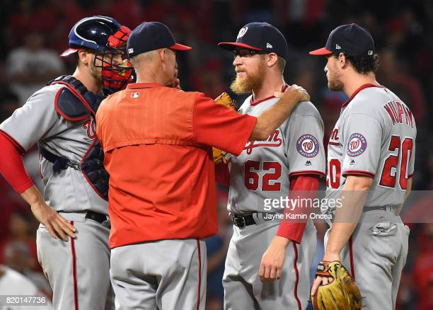 Matt Wieters of the Washington Nationals and Daniel Murphy look on as pitching coach Mike Maddux relief pitcher Sean Doolittle in the ninth inning of...