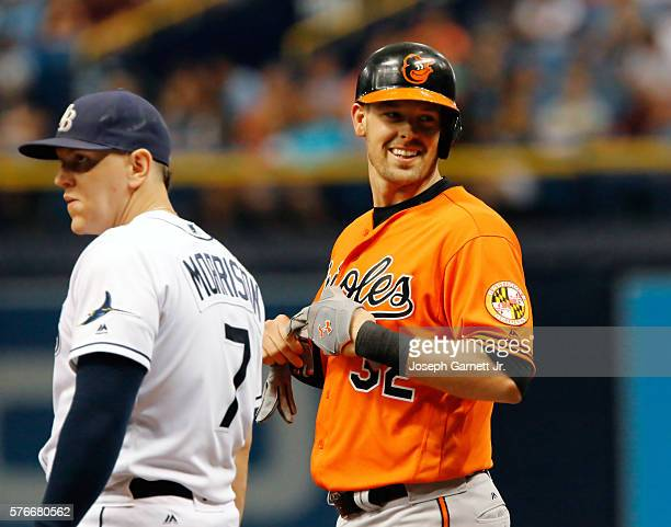 Matt Wieters smiles at a fan after reaching first base during the second inning as Logan Morrison of the Rays watches the infield during the...