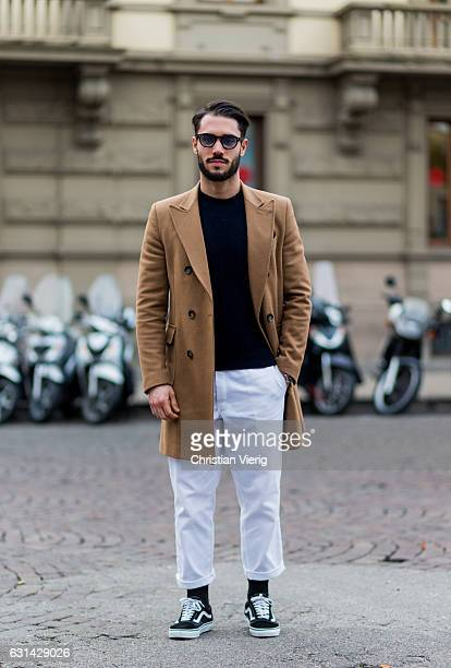 Matteo Bacchi wearing a beige wool coat white pants Vans sunglasses black longshirt on January 10 2017 in Florence Italy
