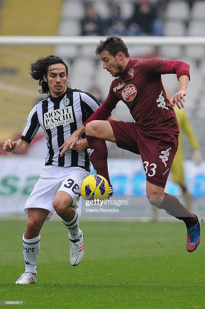 Matteo Brighi (R) of Torino FC in action against <a gi-track='captionPersonalityLinkClicked' href=/galleries/search?phrase=Francesco+Bolzoni&family=editorial&specificpeople=4410646 ng-click='$event.stopPropagation()'>Francesco Bolzoni</a> of AC Siena during the Serie A match between Torino FC and AC Siena at Stadio Olimpico di Torino on January 13, 2013 in Turin, Italy.