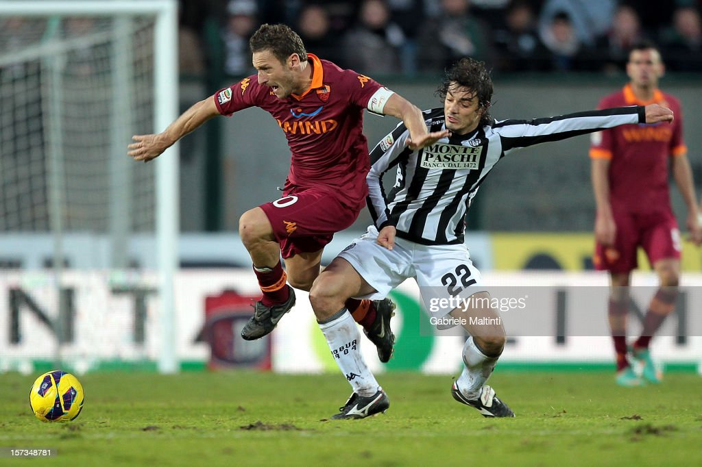 Matteo Contini of AC Siena fights for the ball with <a gi-track='captionPersonalityLinkClicked' href=/galleries/search?phrase=Francesco+Totti&family=editorial&specificpeople=208985 ng-click='$event.stopPropagation()'>Francesco Totti</a> of AS Roma during the Serie A match between AC Siena and AS Roma at Stadio Artemio Franchi on December 2, 2012 in Siena, Italy.