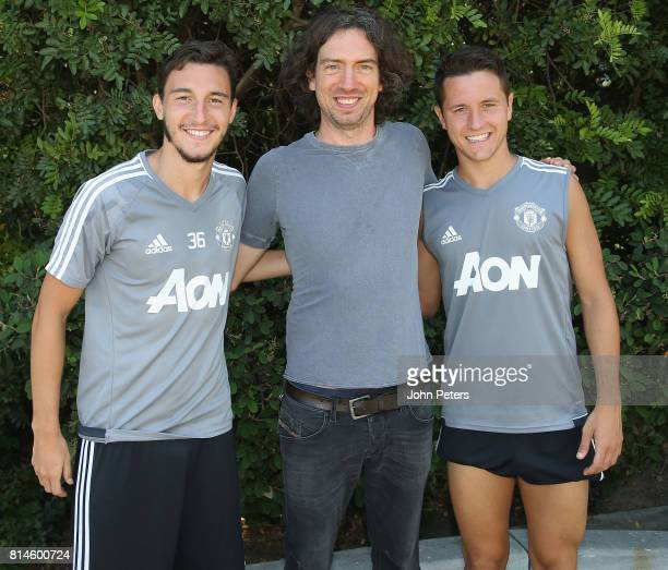 Matteo Darmian and Ander Herrera of Manchester United pose with Gary Lightbody lead singer of Snow Patrol after a first team training session as part...