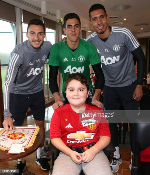 Matteo Darmian Joel Pereira and Chris Smalling of Manchester United pose with Logan during a MU Foundation Dream Day at Aon Training Complex on...