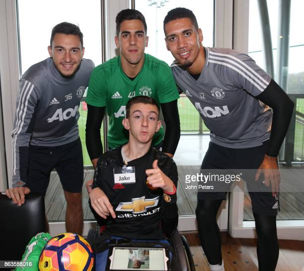 Matteo Darmian Joel Pereira and Chris Smalling of Manchester United pose with Jake during a MU Foundation Dream Day at Aon Training Complex on...