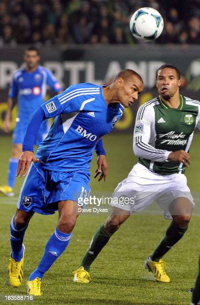 Matteo Ferrari of Montreal Impact heads a ball as Ryan Johnson of Portland Timbers looks on during the second half of the game at JeldWen Field on...