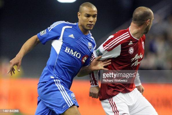 Matteo Ferrari of the Montreal Impact battles for position with Kris Boyd of the Portland Timbers during the MLS match at the Olympic Stadium on...