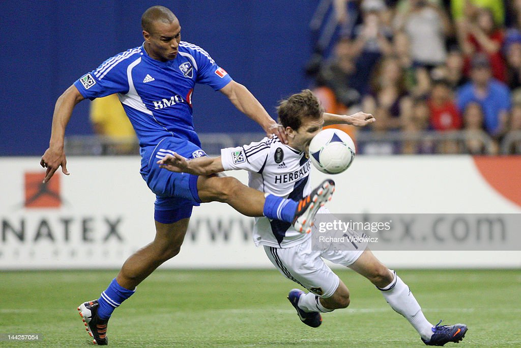 Matteo Ferrari of the Montreal Impact kicks the ball in front of Mike Magee of the Los Angeles Galaxy during the MLS match at the Olympic Stadium on...