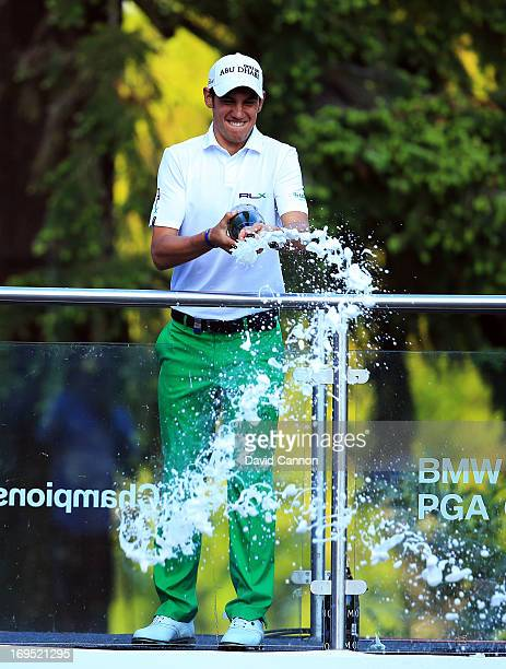 Matteo Manassero of Italy celebrates victory with a bottle of champagne behind the eighteenth green following the final round of the BMW PGA...