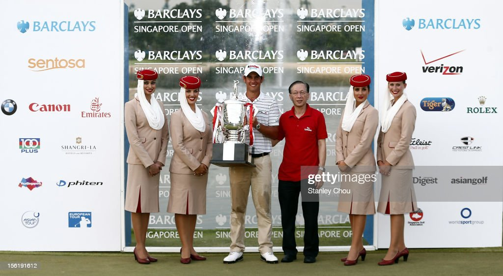 Matteo Manassero of Italy poses for photographs with the Barclay's Singapore Open Champion Trophy and the Emirates Air Stewardess and Official, after winning the playoff during the fourth round of the Barclays Singapore Open at the Sentosa Golf Club on November 11, 2012 in Singapore. Singapore.