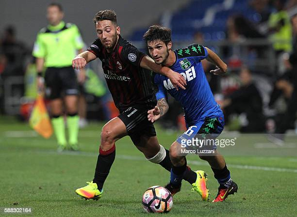 Matteo Politano of US Sassuolo Calcio is challenged by Andrea Bertolacci of AC Milan during the TIM Preseason Tournament at Mapei Stadium Citta' del...