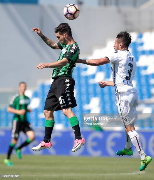 Matteo Politano of US Sassuolo Calcio jumps for the ball with Mauricio Isla of Cagliari Calcio during the Serie A match between US Sassuolo and...