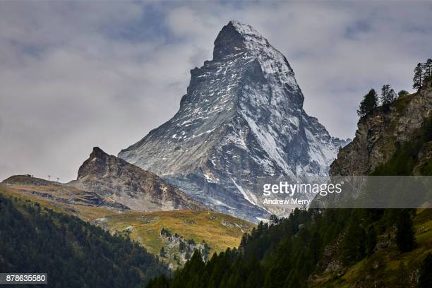 Matterhorn a classic view, snow capped with clouds and pine trees. Zermatt, Switzerland.