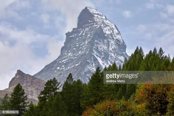 Matterhorn snow-capped with pine forest and clouds, taken from Zermatt. A classic Swiss landscape.