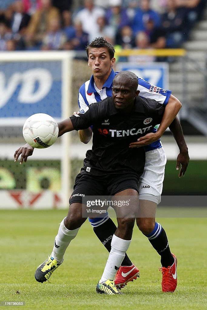 Matthew Amoah of Heracles Almelo (R), Chris Kum of SC Heerenveen (L) during the Dutch Eredivisie match between sc Heerenveen and Heracles Almelo on August 18, 2013 at the Abe Lenstra stadium in Heerenveen, The Netherlands.