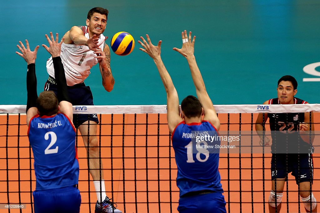 Matthew Anderson of the United States spikes the ball against Uros Kovacevic and Marko Podrascanin of Serbia during the FIVB World League Group 1...